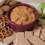 pumpkin dip on cutting board with ginger snaps, pretzels, apples and crackers